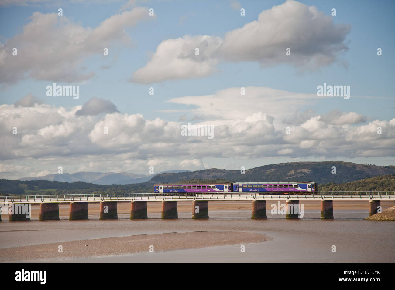 A commuter train crosses the railway bridge that crosses the river dart at Arnside, in Cumbria,as white clouds scurry - Stock Image