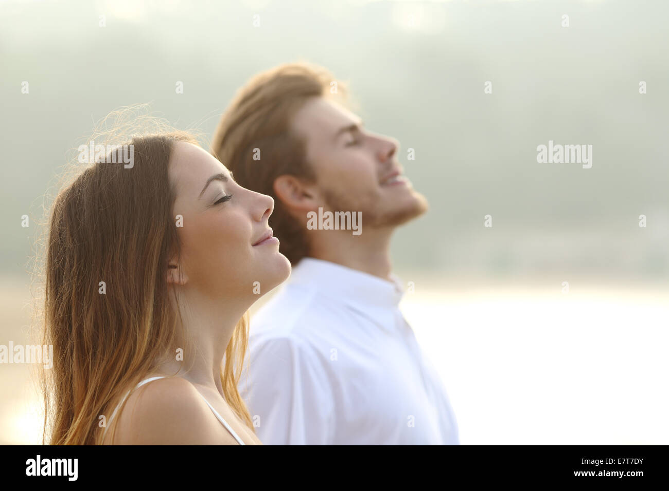 Profile of a couple of man and woman breathing deep fresh air together at sunset - Stock Image