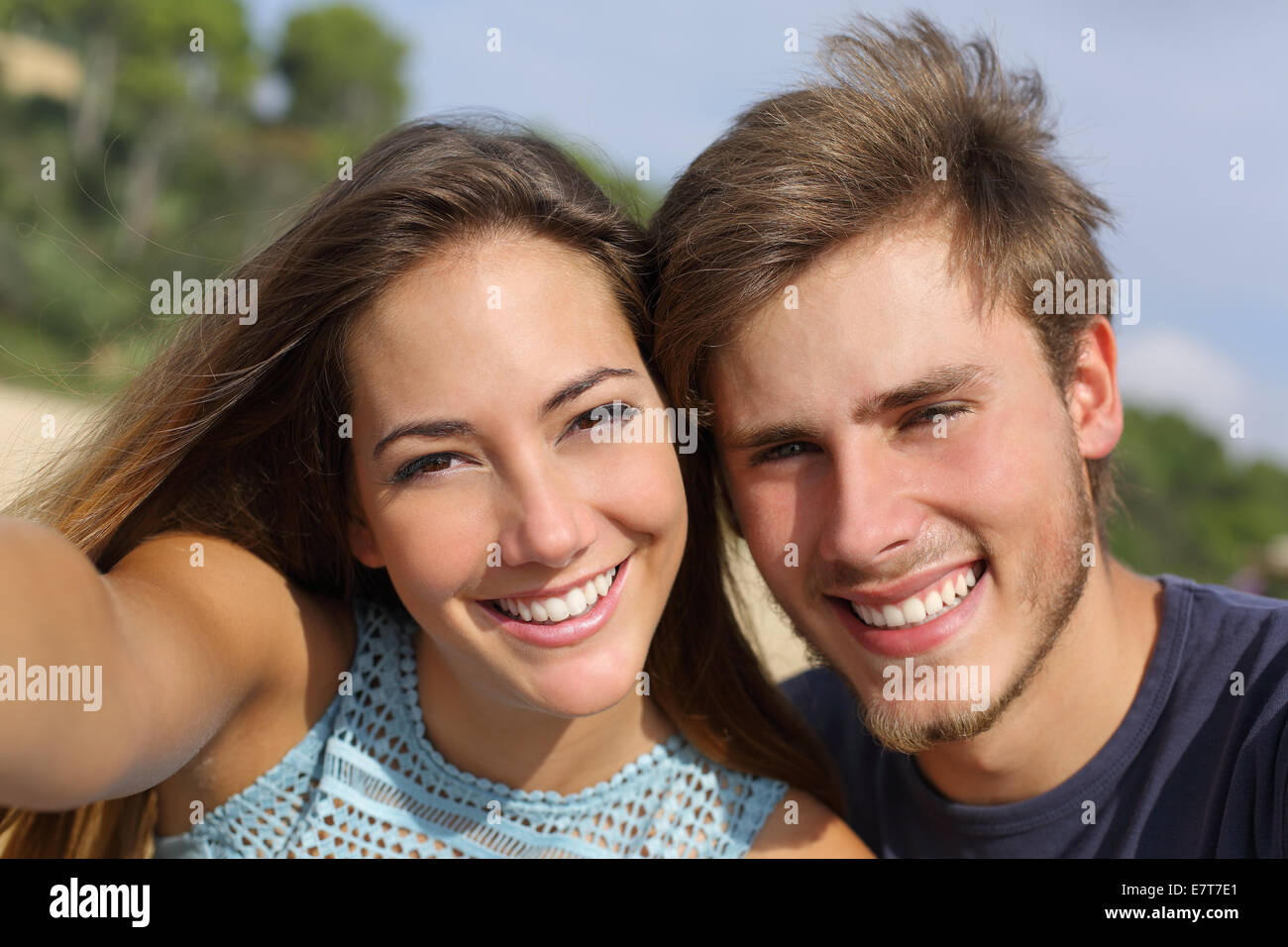 Couple photographing a selfie with the smart phone or digital camera outdoors in the mountain - Stock Image