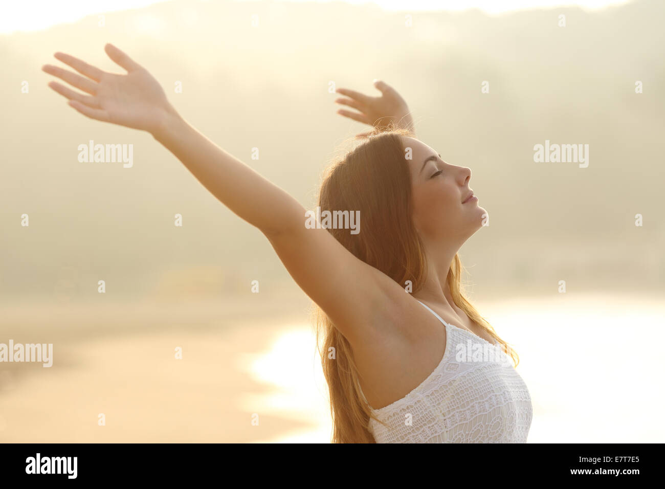 Relaxed woman breathing fresh air raising arms at sunrise with a warmth golden background - Stock Image