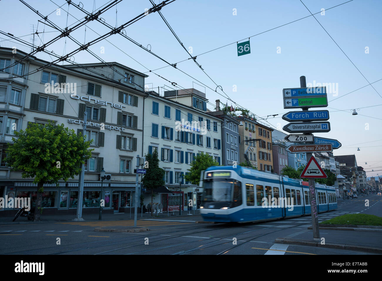 A view down Limmatquai in Zürich at dawn with a moving tram and overhead lines. - Stock Image