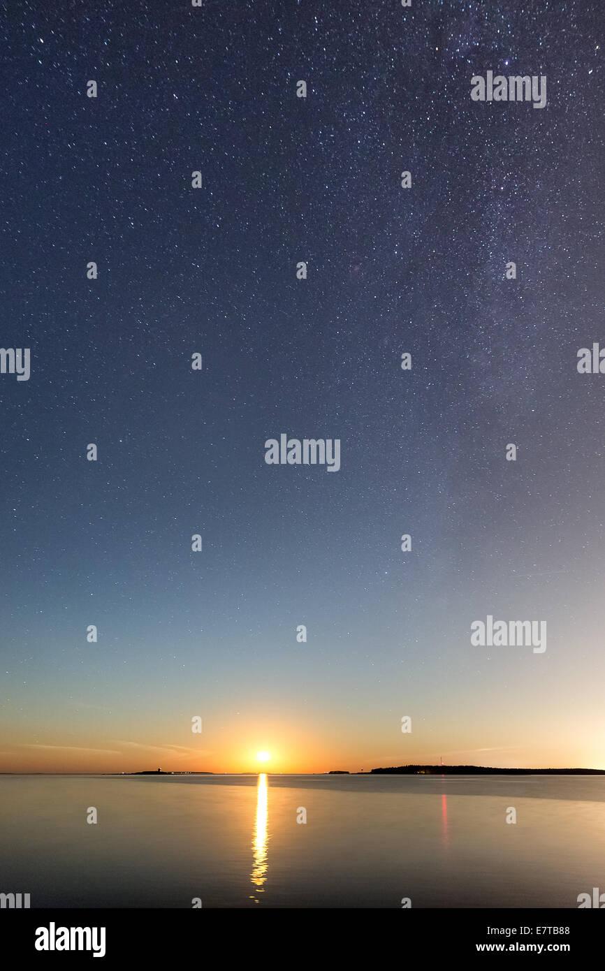 Setting reddish moon seen from Hattusaari island, Helsinki, Finland, Europe, EU - Stock Image