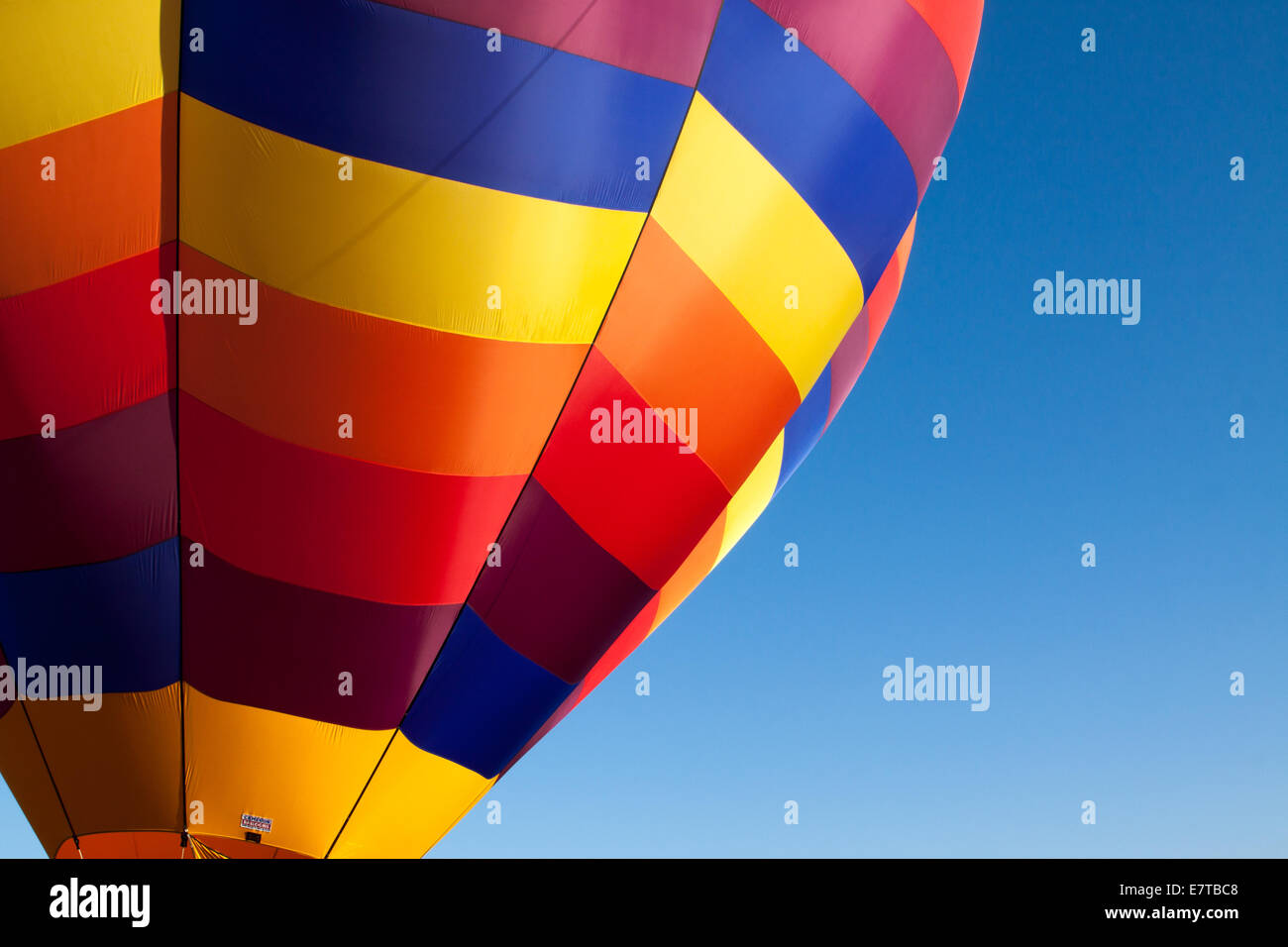 A bright jewel-toned hot air balloon is readied for launch - Stock Image