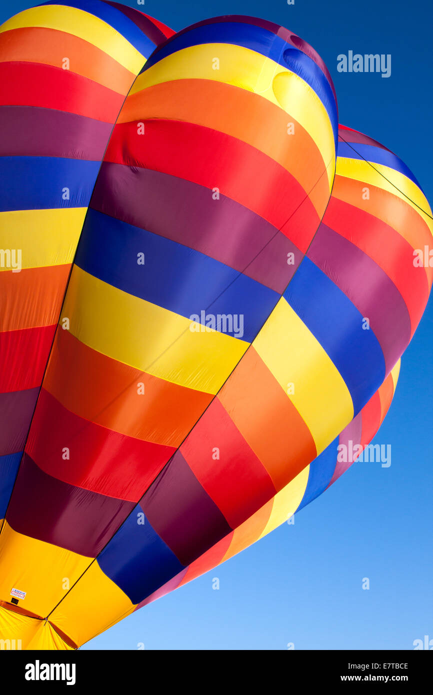 The bright jewel-toned canopy of a hot air balloon being readied for launch against a blue sky - Stock Image
