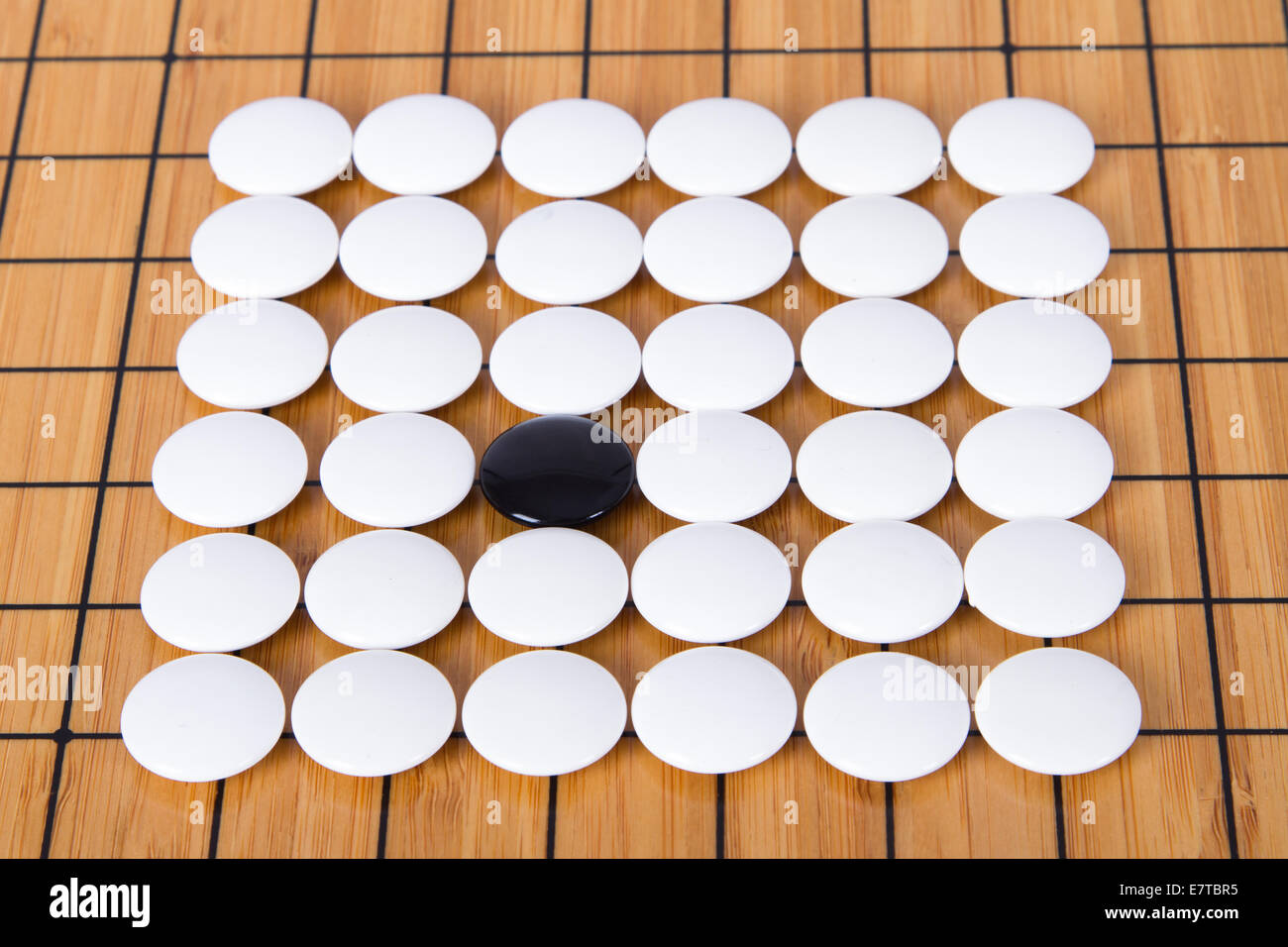Black Stone Standing Out From White Pieces On Chinese Go Game Board