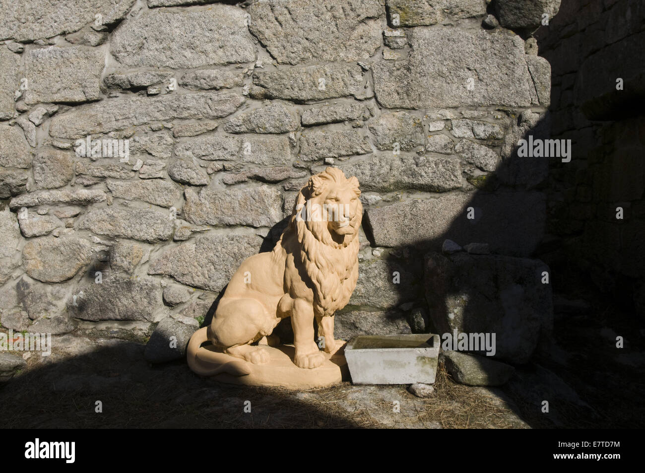 clay lion and a stone wall in a rural village in northern Portugal - Stock Image