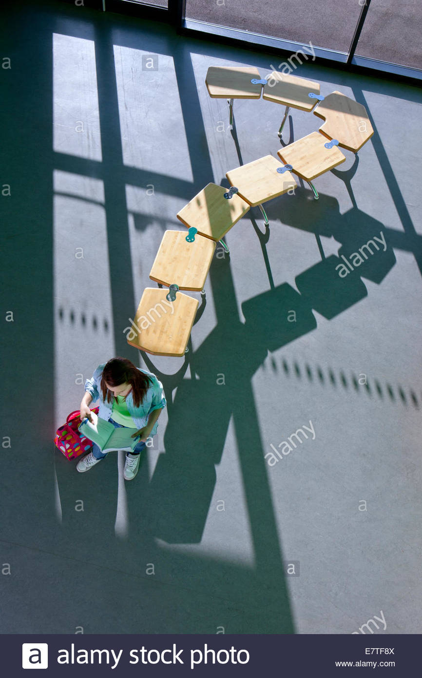 Student standing near row of school desks formed into a question mark symbol - Stock Image