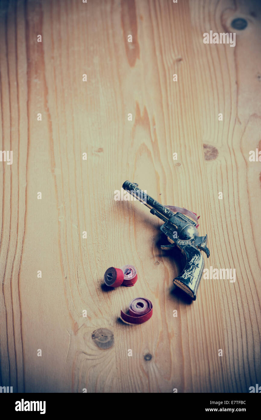 Child's Toy Cap Gun and caps on a wooden table. Vintage style Stock Photo