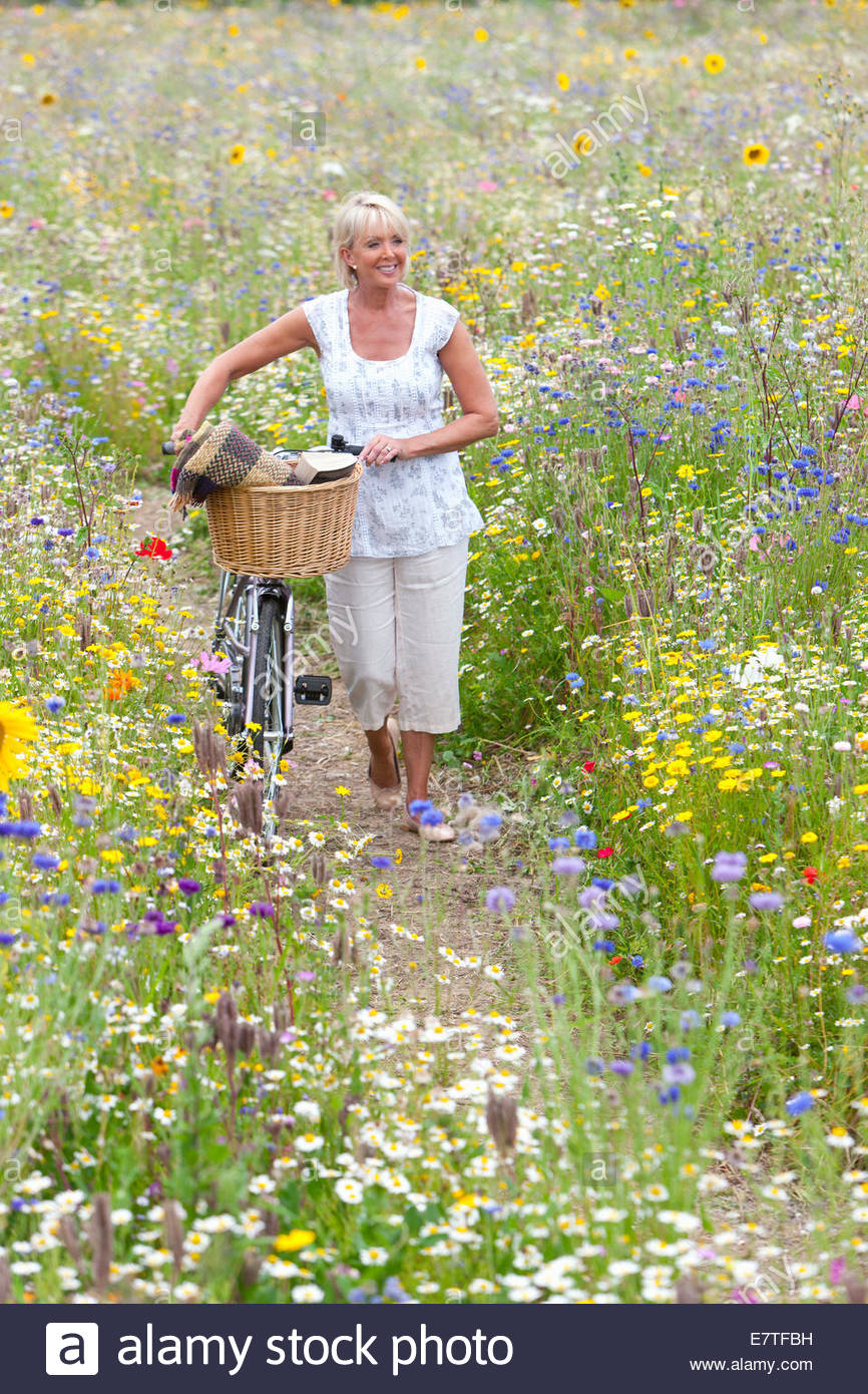 Woman pushing bicycle on path through wildflowers in field Stock Photo