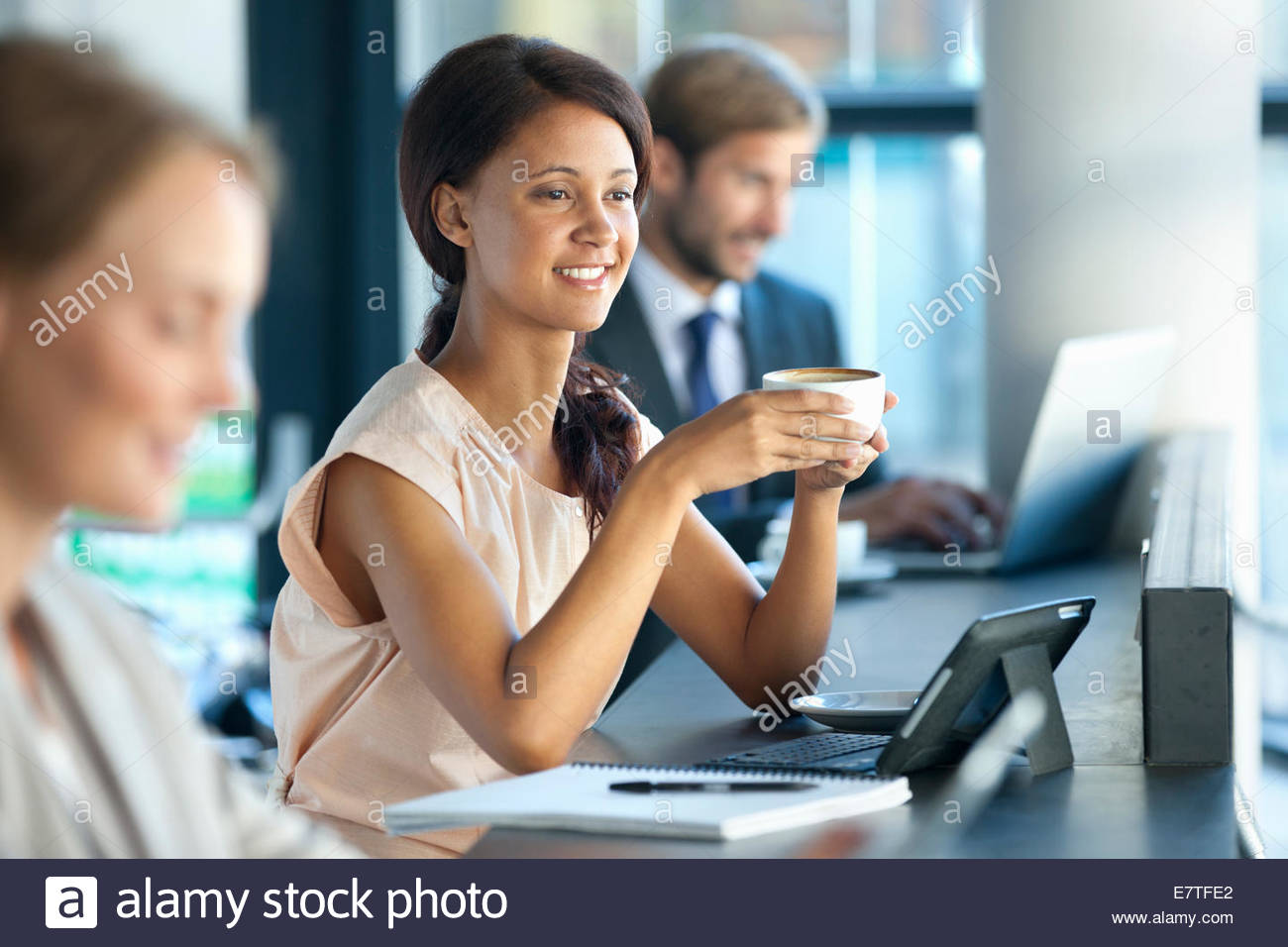 Smiling businesswoman drinking coffee in coffee shop - Stock Image