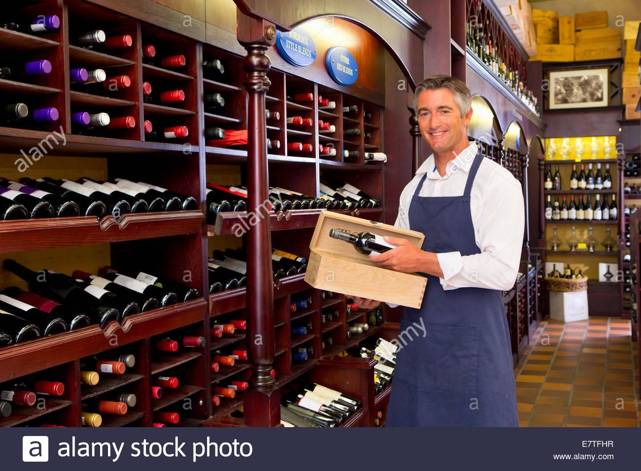 Worker stocking bottles in wine shop - Stock Image