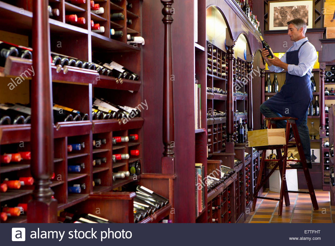 Worker on ladder stocking bottles in wine shop - Stock Image