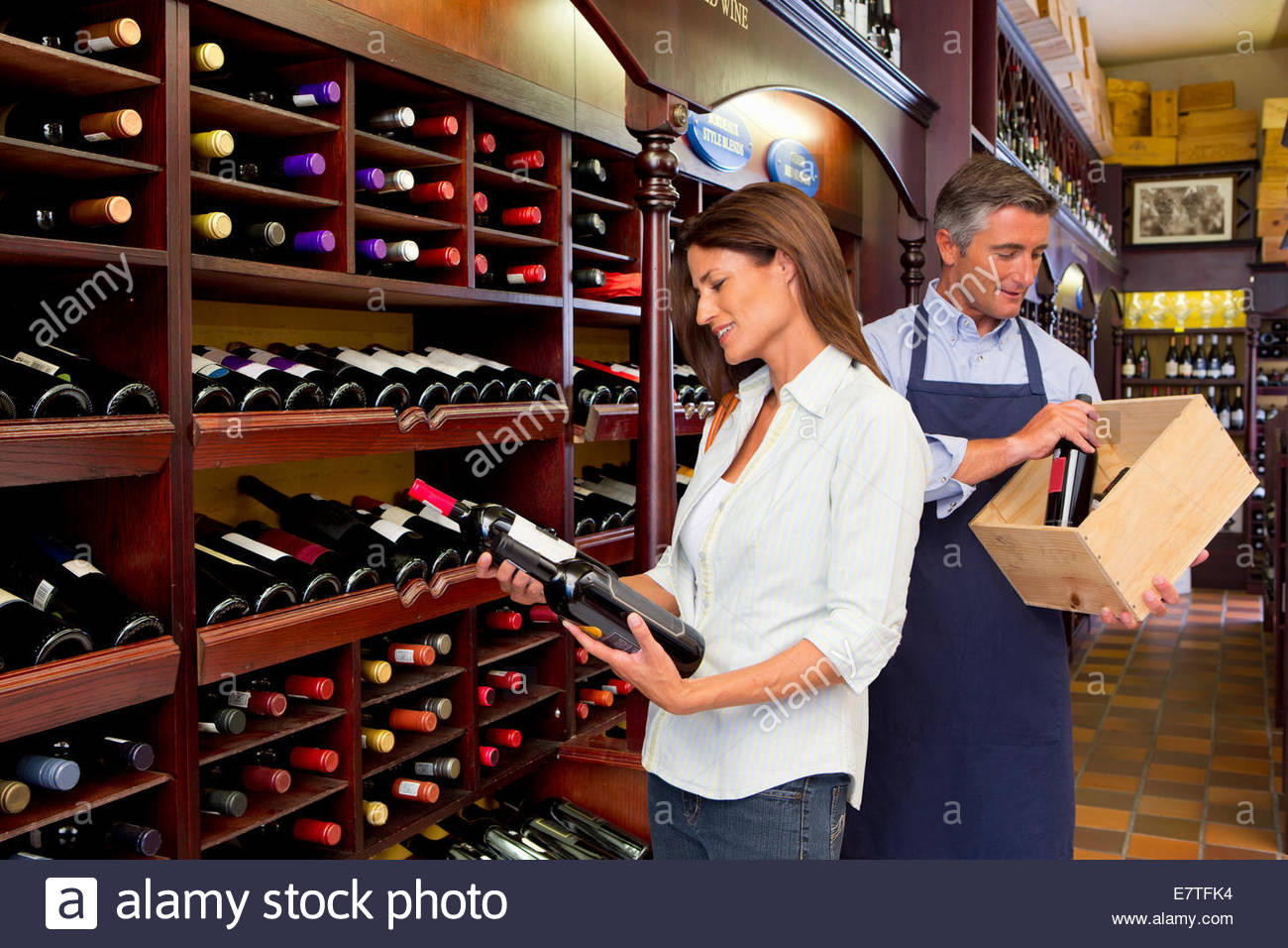 Smiling customer and  worker examining bottles in wine shop Stock Photo