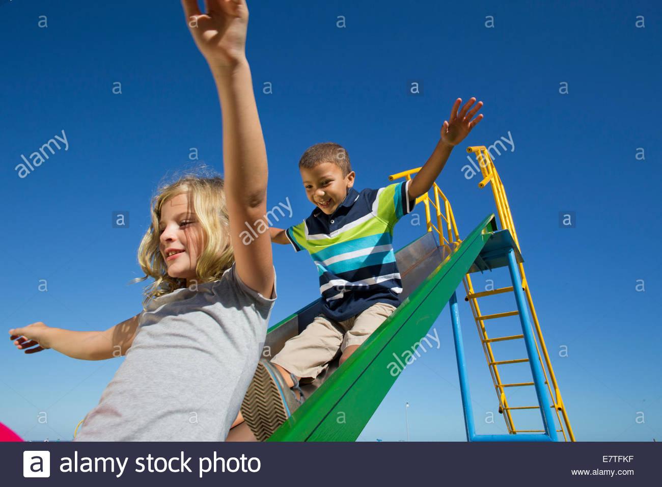 Smiling children sliding on slide Stock Photo