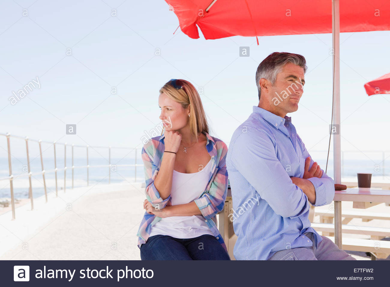 Couple arguing under umbrella at waterfront table - Stock Image