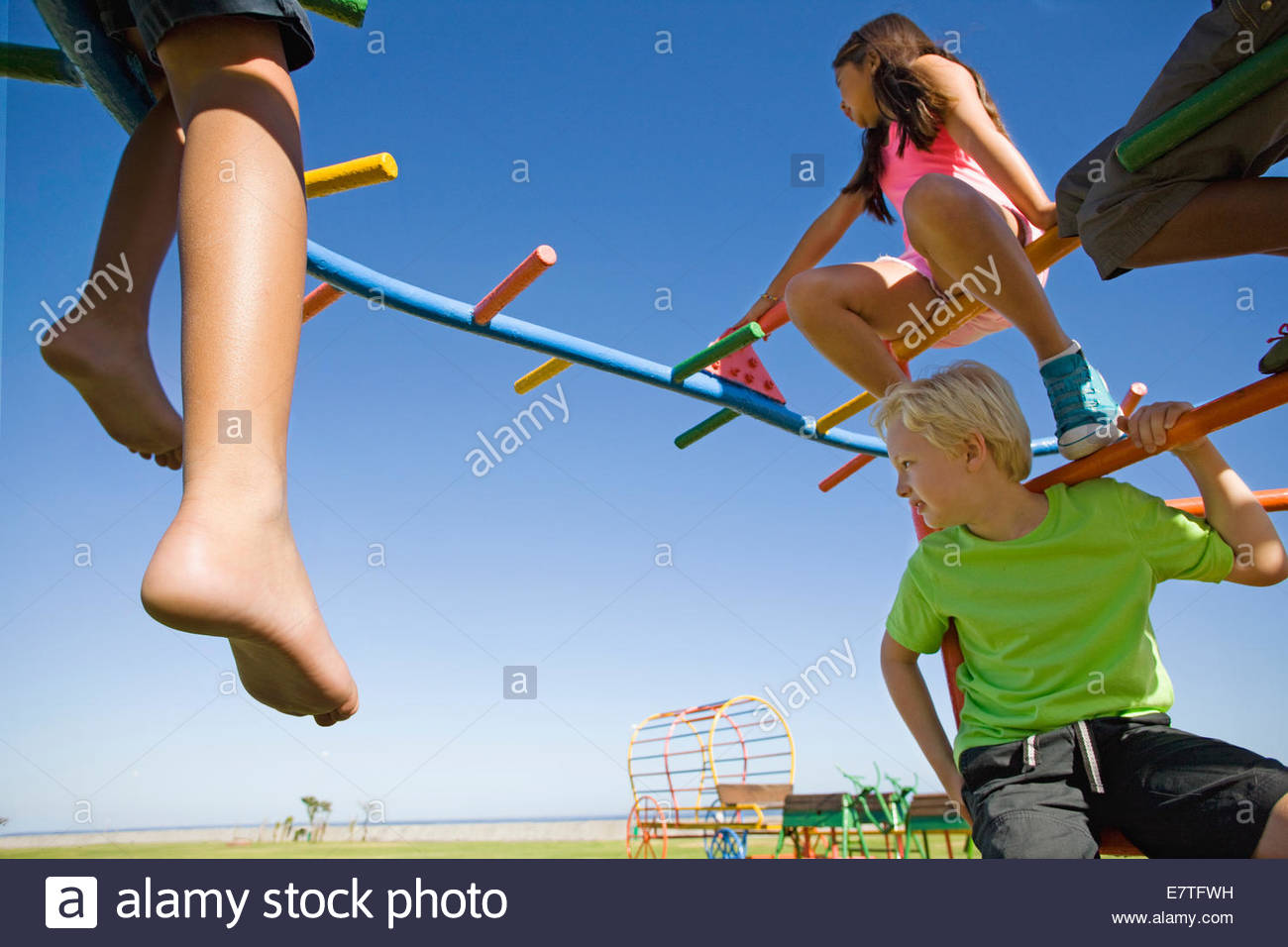 Children sitting on monkey bars at playground Stock Photo