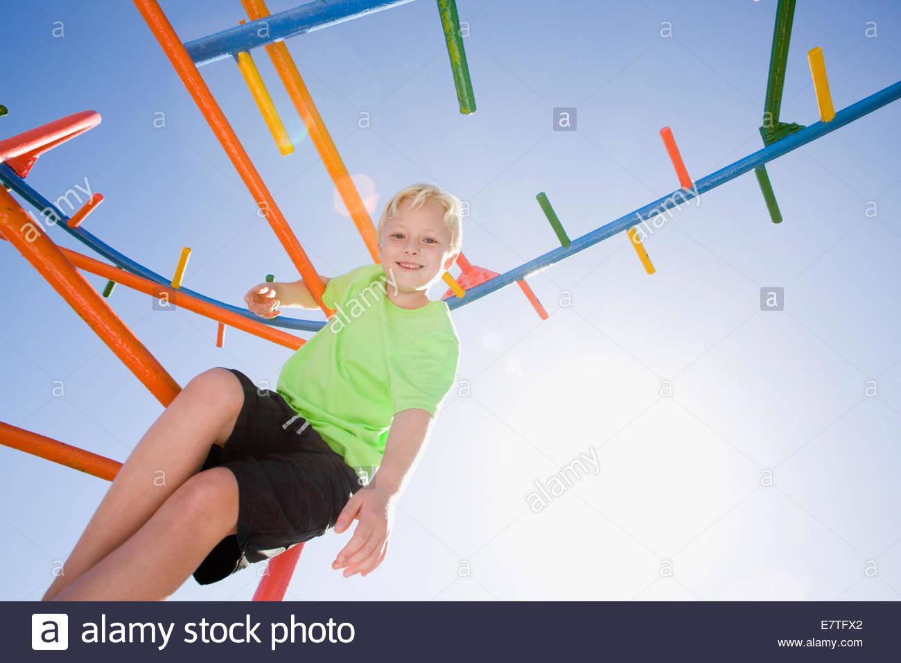 Smiling boy playing on monkey bars at playground - Stock Image