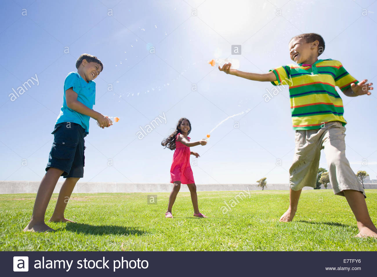 Children squirting water at each other at park - Stock Image