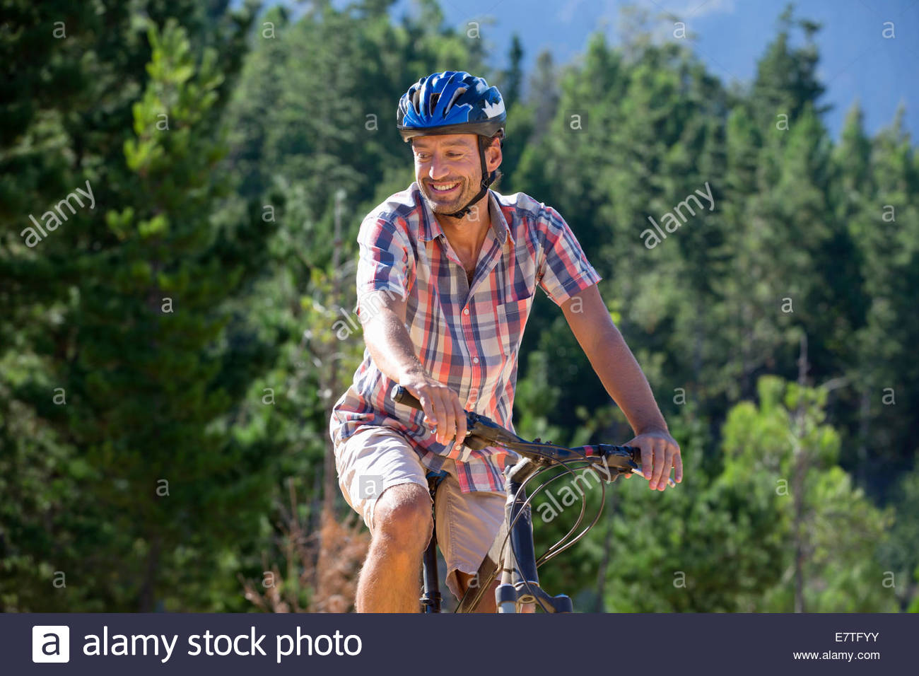 Man riding mountain bike in forest - Stock Image