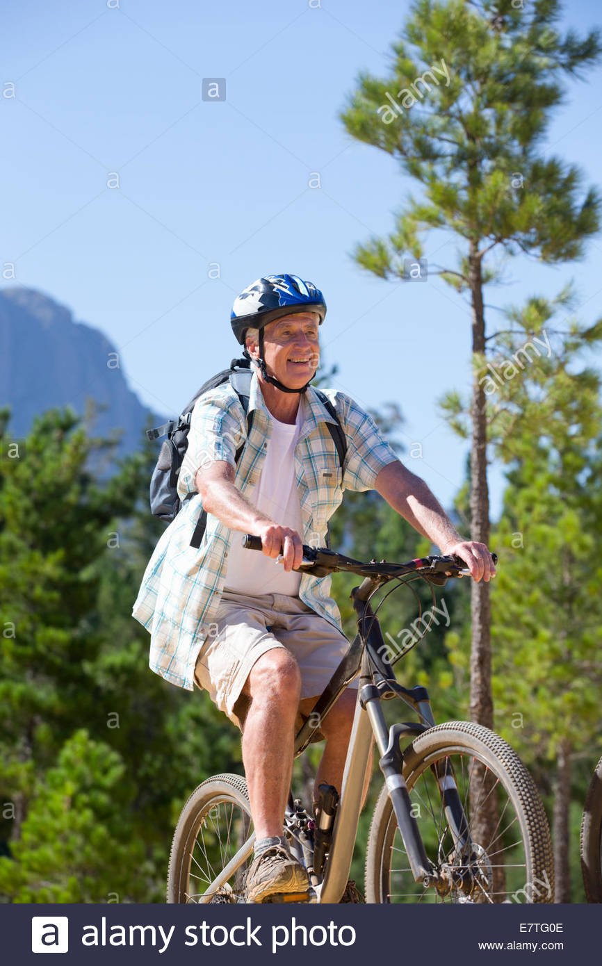 Older man riding mountain bikes in forest - Stock Image