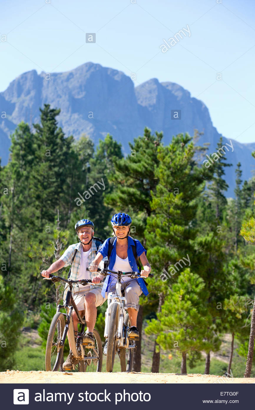 Older couple riding mountain bikes in forest - Stock Image