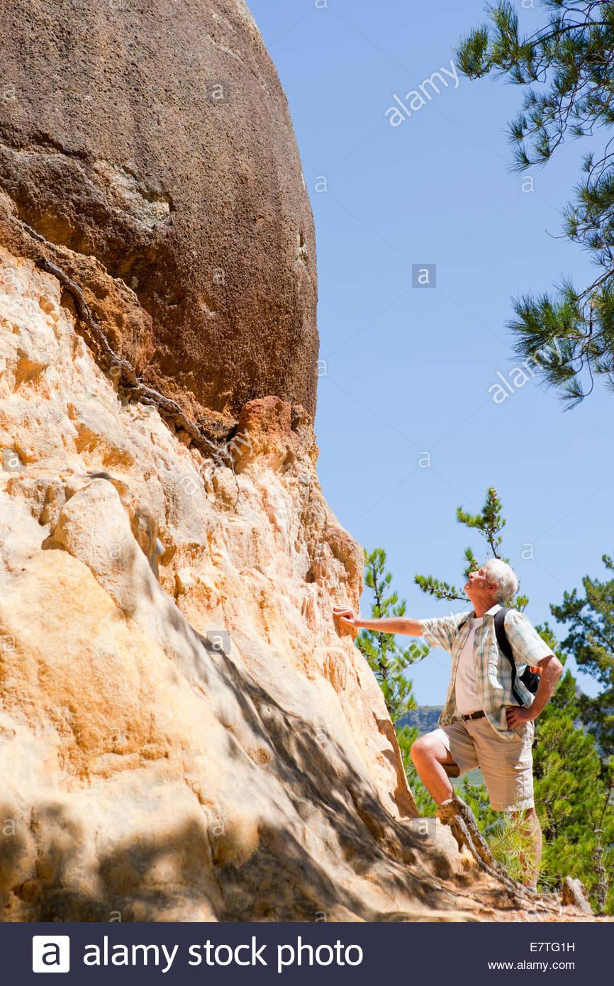 Older man admiring rock formation on rural hillside - Stock Image