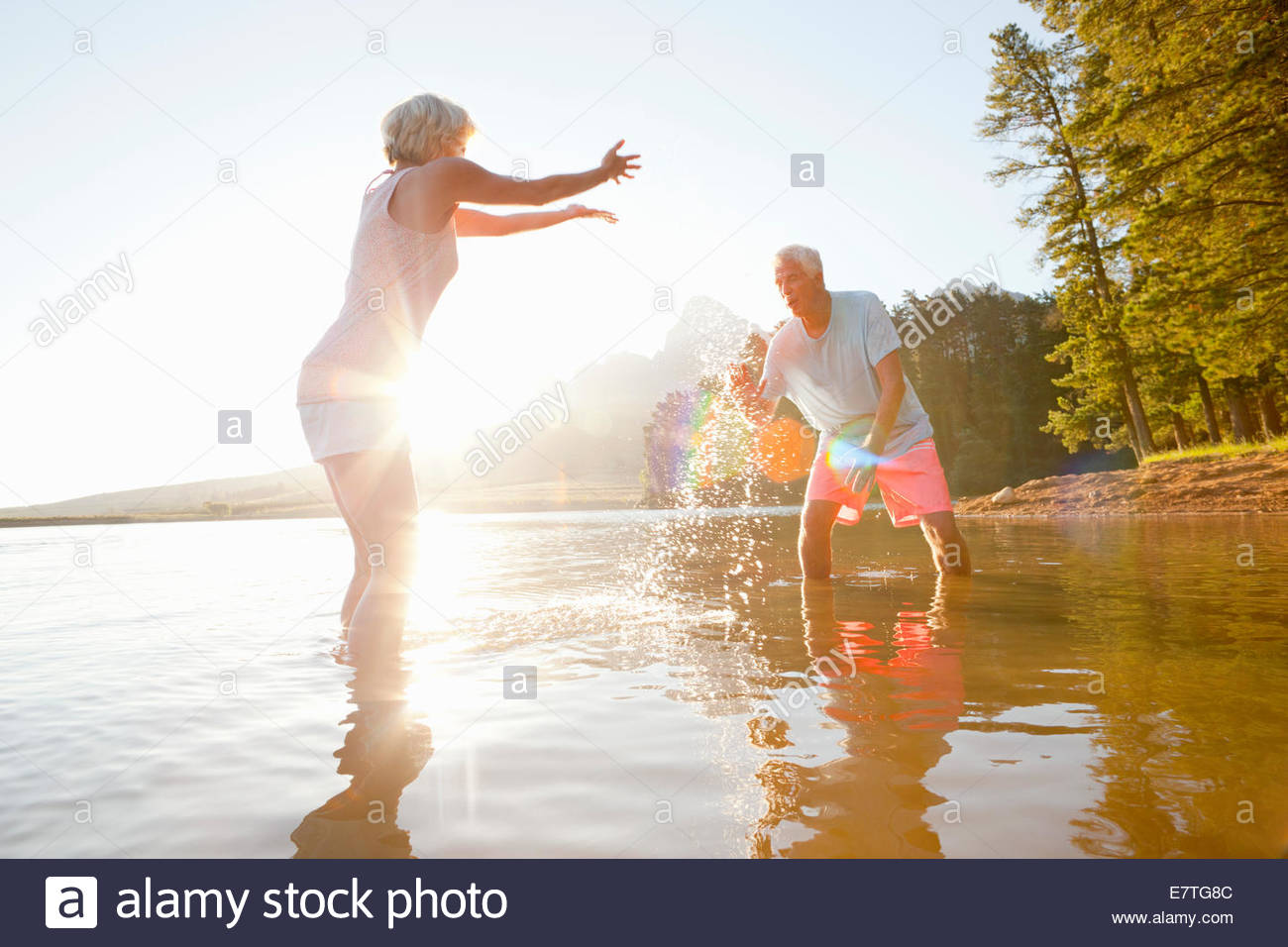 Older couple splashing each other in lake - Stock Image