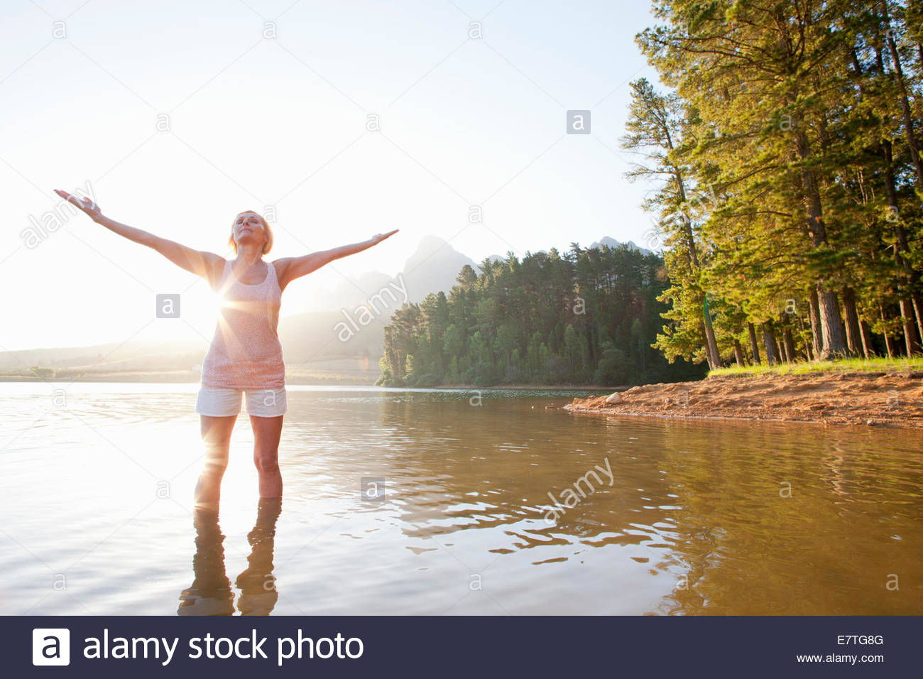 Older woman standing with arms outstretched in lake - Stock Image