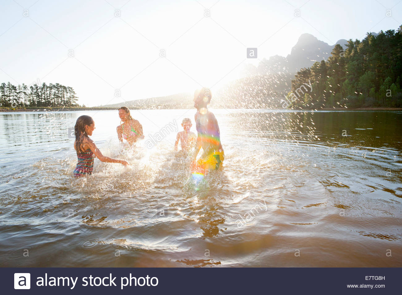 Family splashing each other in lake - Stock Image