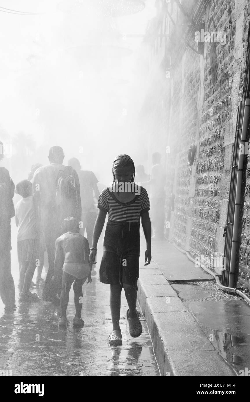 Young girl emerging from a crowd in the rain - Stock Image