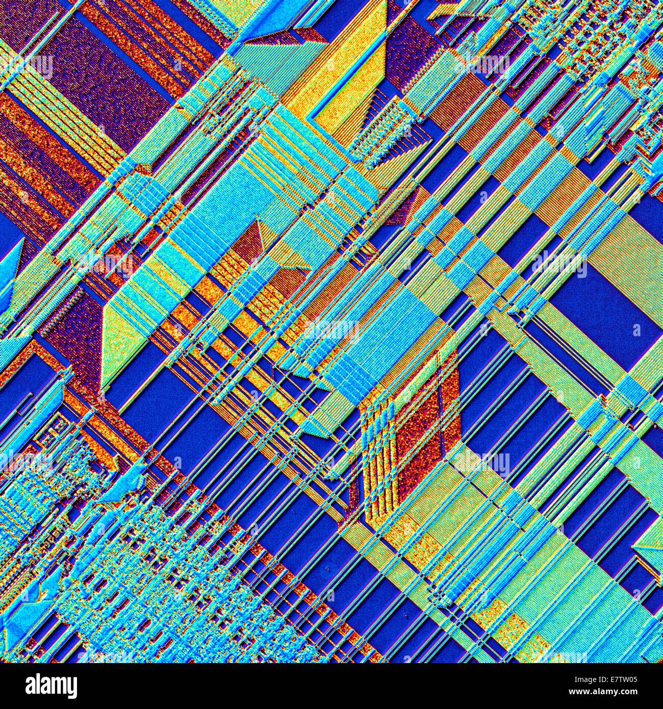 Computer chip. Coloured light micrograph of the surface of an integrated chip from a computer. This integrated circuit - Stock Image