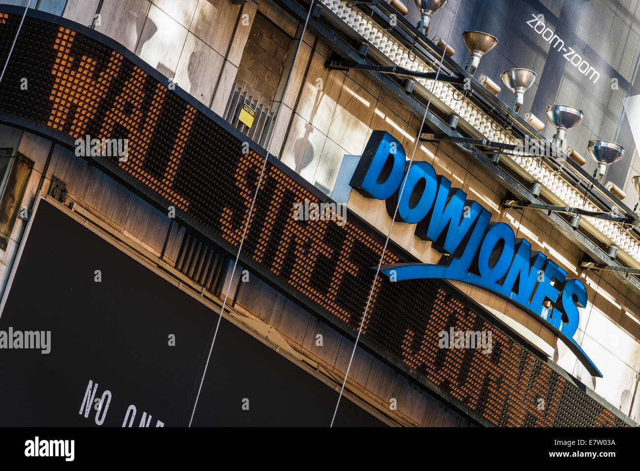 A neon sign displays the latest Wall Street Journal headlines under the Dow Jones logo in Times Square, Midtown - Stock Image