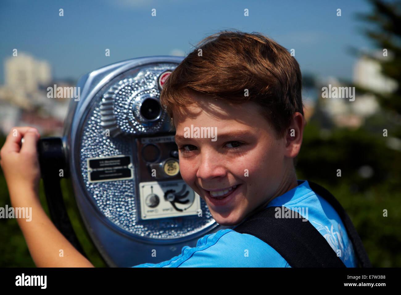 Boy using coin-operated binoculars, Telegraph Hill, San Francisco, California, USA - Stock Image