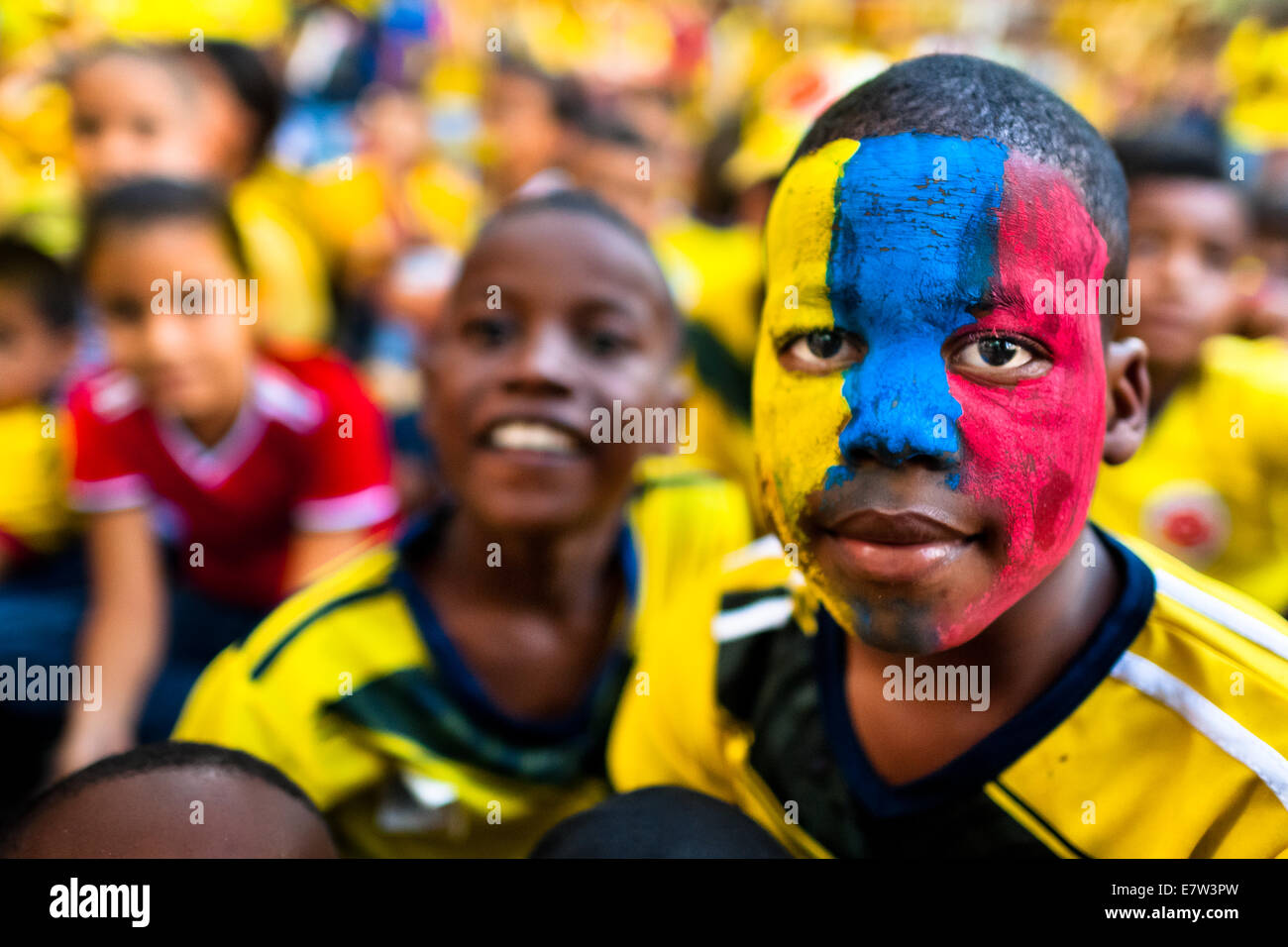 Colombian boys watch the football match at the FIFA World Cup 2014, in a park in Cali, Colombia. - Stock Image