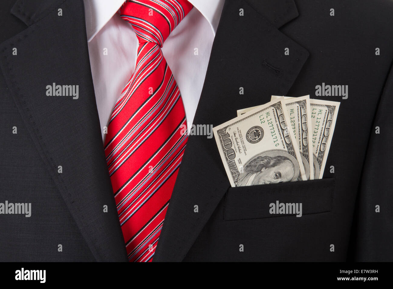 Smart businessman with earned money in suit pocket. - Stock Image