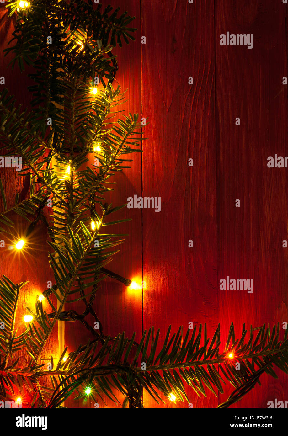 christmas rustic background vintage red planked wood with lights and fir twigs and free text space