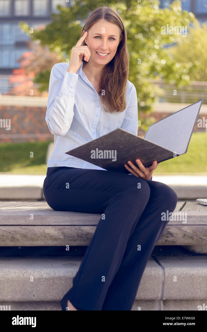 Smiling attractive businesswoman having an idea while reading a business folder in a park - Stock Image