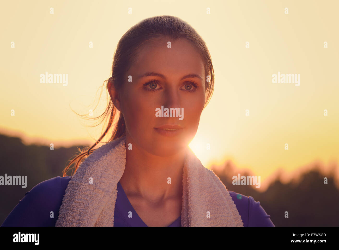 Attractive woman outdoors at sunset backlit by the orange glow of the sun causing a flare around her face - Stock Image