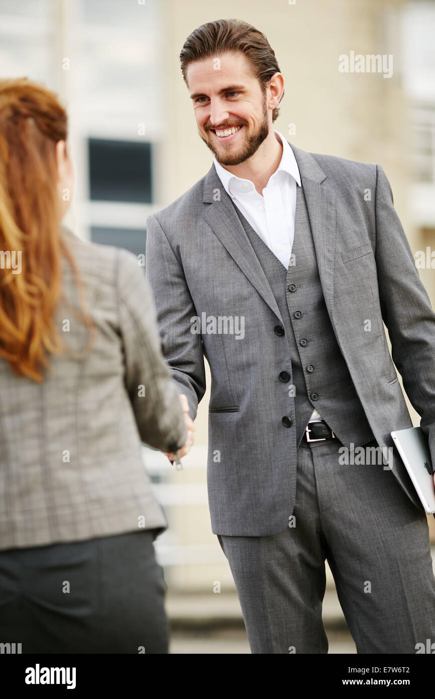 Two business people greeting each other - Stock Image