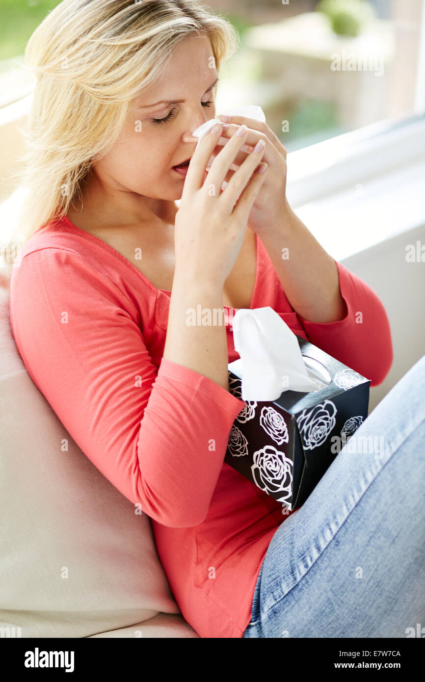 Woman feeling ill with a cold - Stock Image