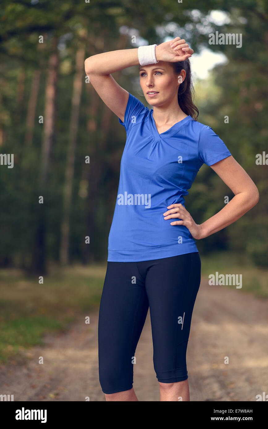 Woman athlete wiping sweat from her forehead onto her wristband as she pauses during her training exercises on a - Stock Image