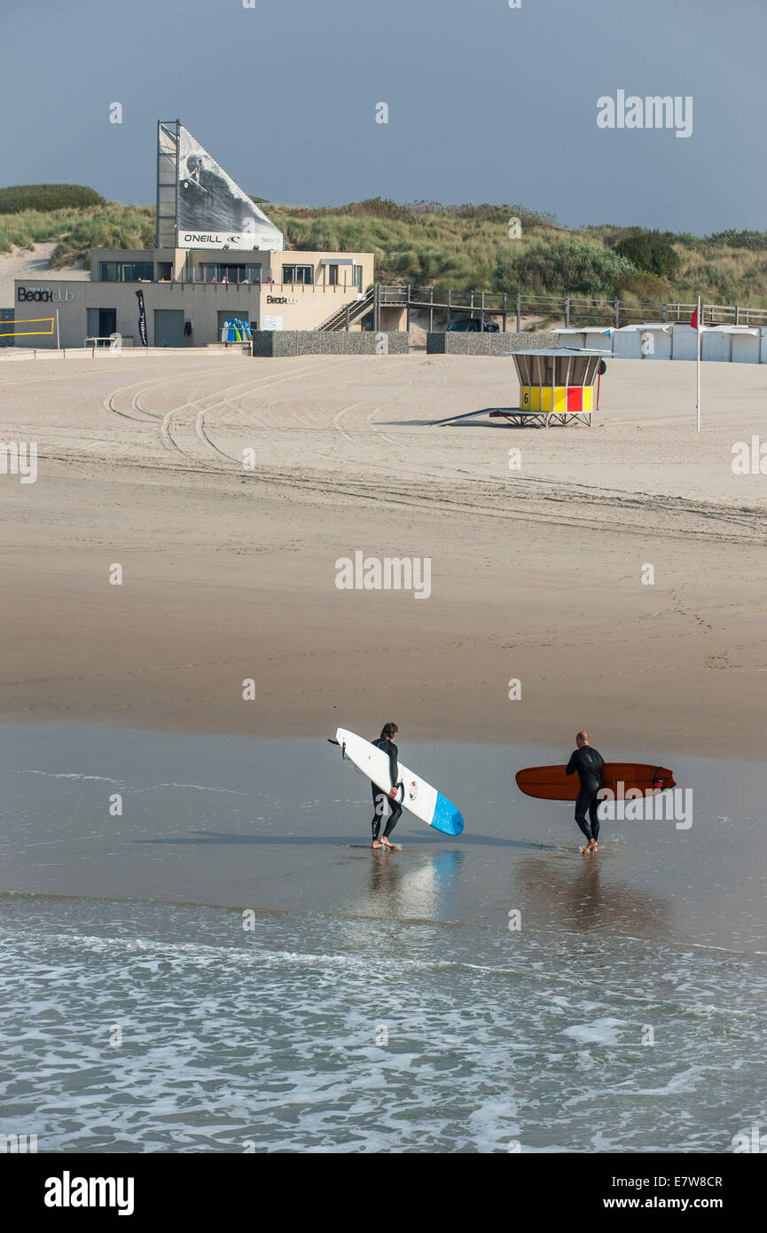 Two surfers leaving the water and walking to the O'Neill Beach club along the North Sea in Blankenberge, Belgium - Stock Image