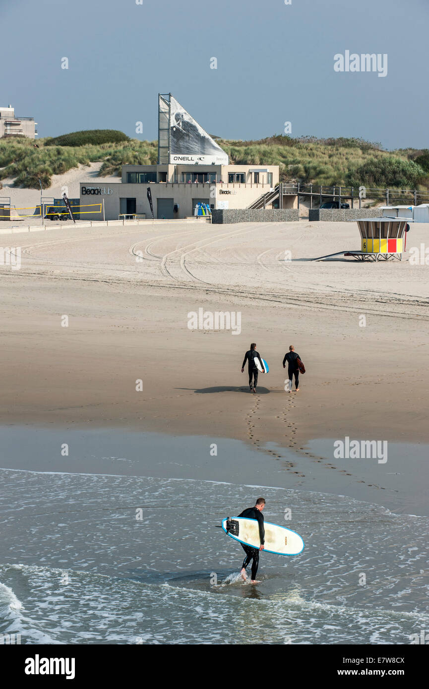 Three surfers leaving the water and walking to the O'Neill Beach club along the North Sea in Blankenberge, Belgium - Stock Image
