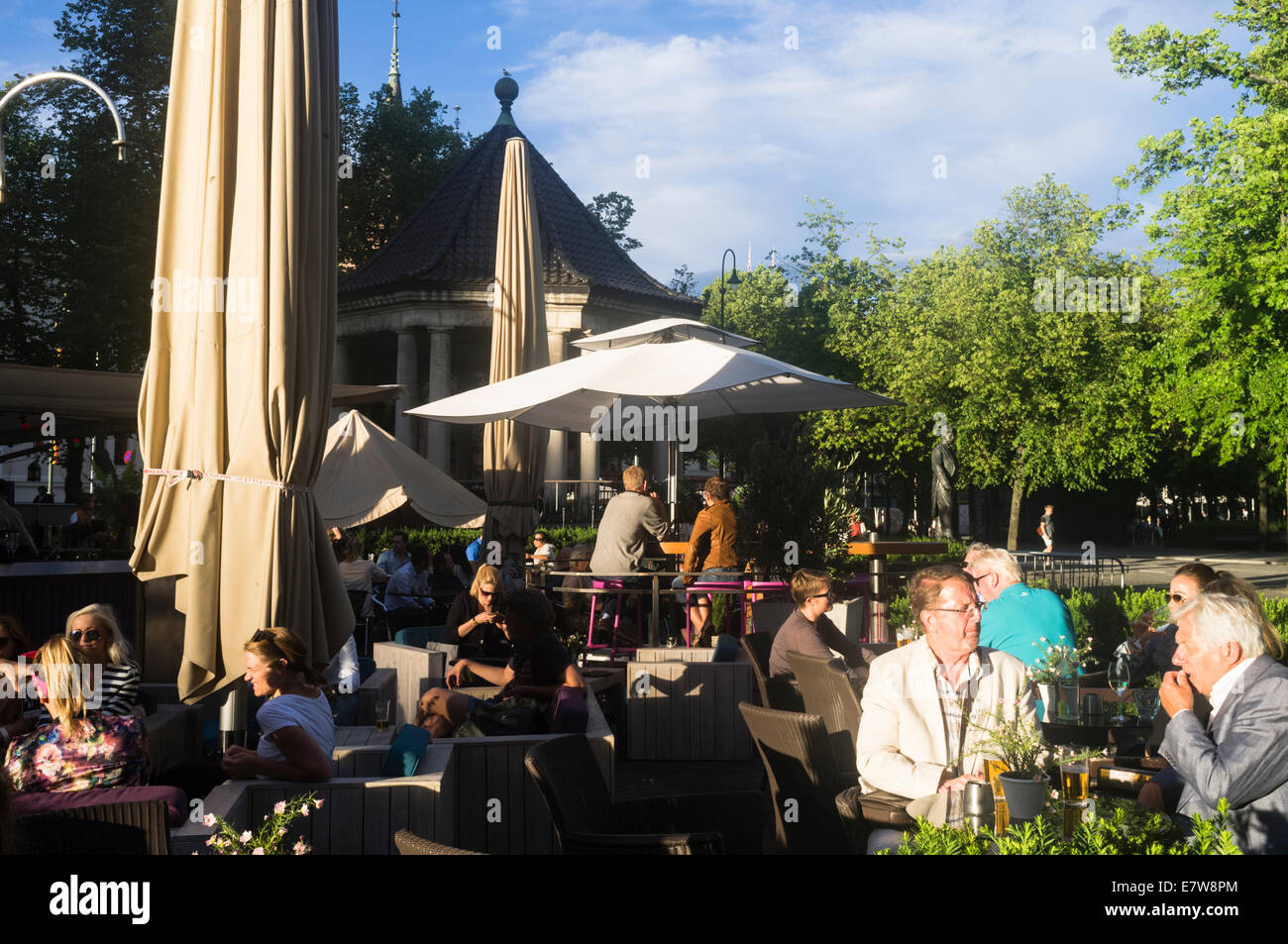People at an open air bar terrace in a park near Karl Johans Gate. Oslo, Norway - Stock Image
