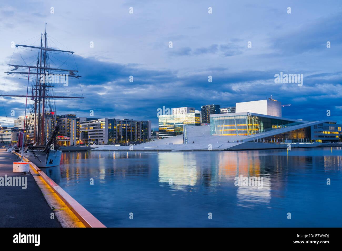 Oslo Opera Hall and sailboat at dusk, Norway - Stock Image