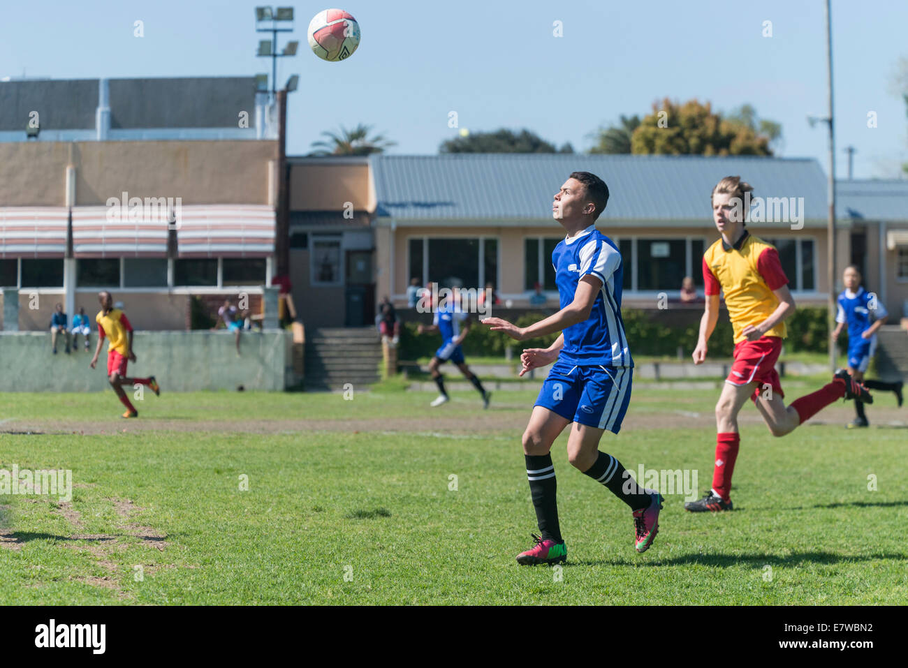 Young football player looking at the flying ball, Cape Town, South Africa - Stock Image