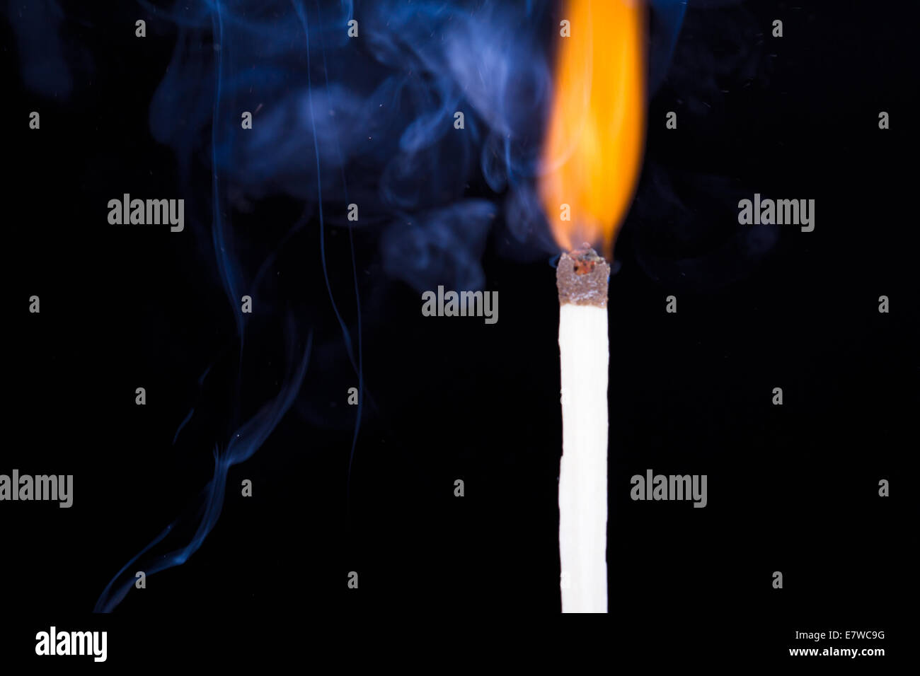 Burning match flame and smoke on dark background. - Stock Image