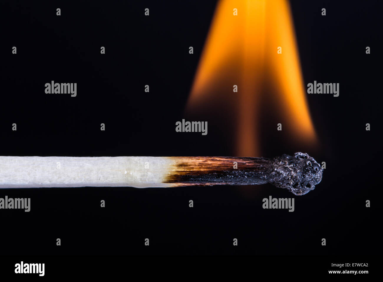 Close up of burning, flaming match on fire against black background. - Stock Image