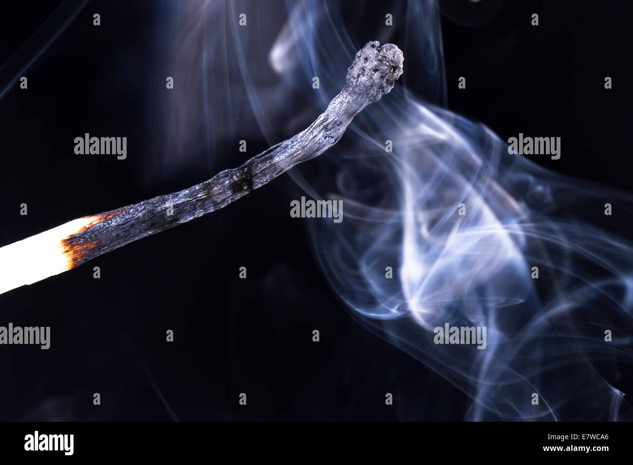 Burnt match with smoke on dark background. - Stock Image
