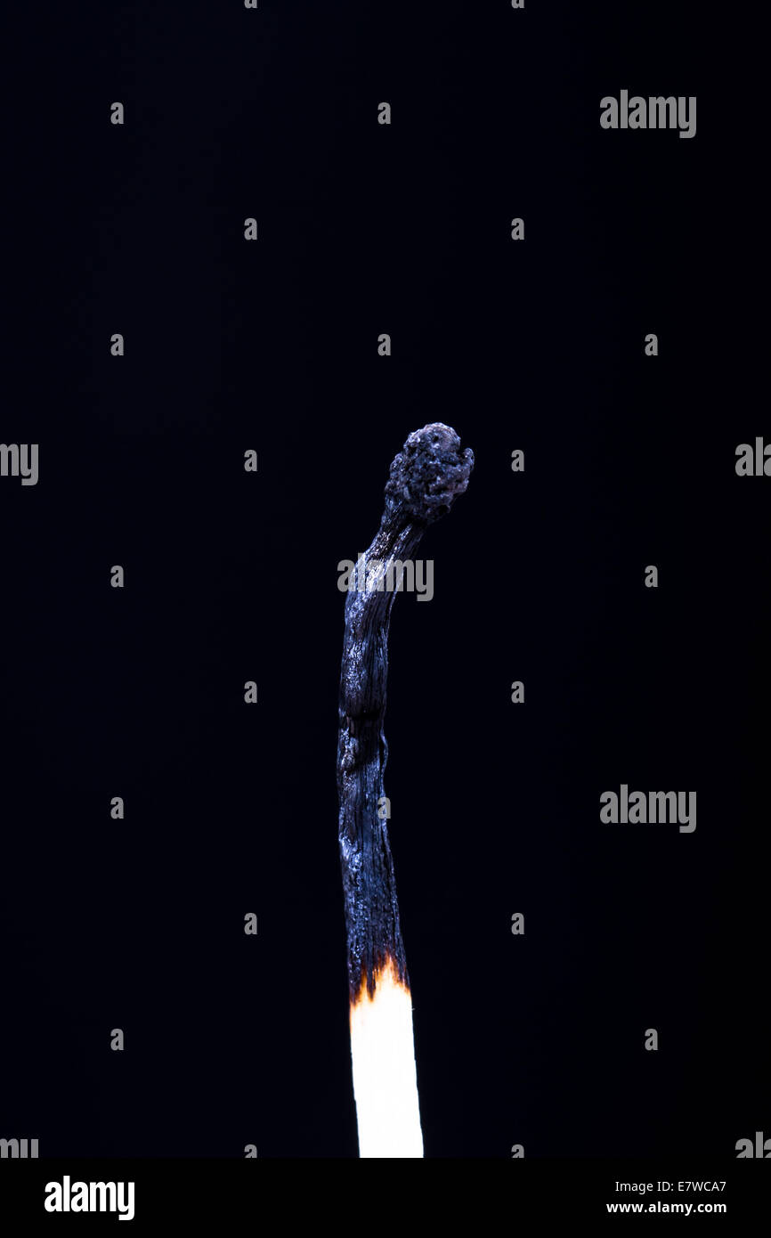 Burnt match on dark background. - Stock Image